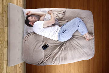 man snoozing modern cell phone alarm clock