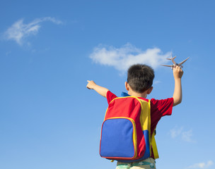 little boy holding a airplane toy and point to sky