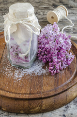 Lilac flowers and sugar on a wooden board