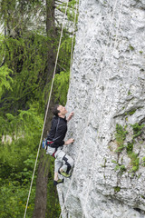 Man climbing steep and high rocky wall.