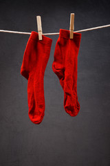 Old red socks hanging on rope