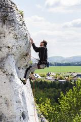 Man climbing natural difficult rocky wall.
