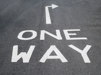 one way sign on tarmac road with arrow pointing right