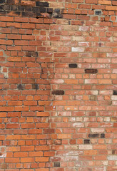 distressed looking wall showing repairs with new bricks