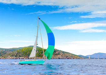 Sailing boat with a green blue spinnaker out of Poros in Greece
