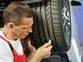 Car mechanic checks the tread pattern of a tire