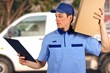 Handsome young delivery man carrying carton box