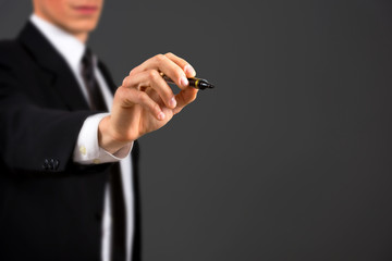 Business male hand holding marker,isolated on dark background.