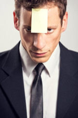 Young businessman with blank note on his forehead.