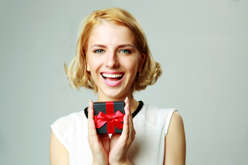Laughing beautiful young woman holding jewelery gift box
