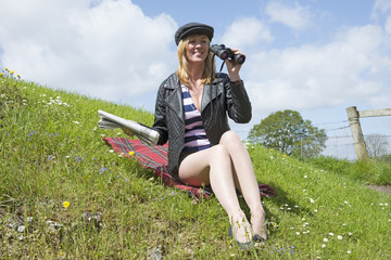 Woman sitting on grass holding racing paper and using binoculars