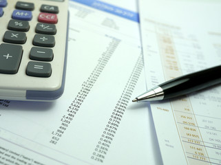 pen and calculator on financial documents