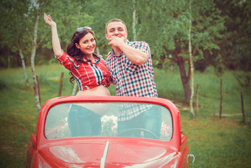 Happy couple in retro red car