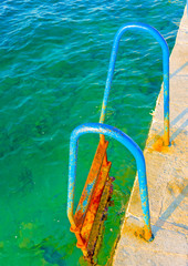 Ruined blue painted old iron made steps to the sea