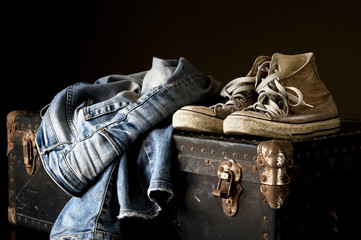 Pair of jeans and sneakers on an old suitcase
