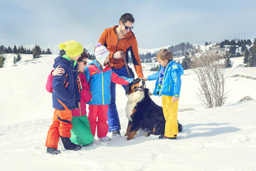 big family with dog having fun in the snow