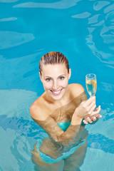 Frau trinkt Sekt im Pool vom Hotel