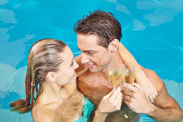 Paar im Pool stößt an mit Champagner