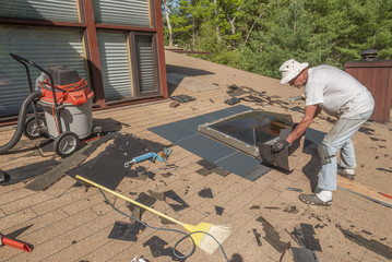 Senior man repairing a skylight on his roof