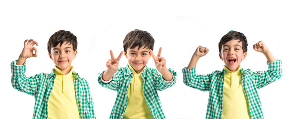 Boy making a victory sign over white background