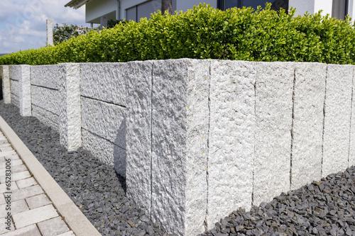 Leinwanddruck Bild Neue Granitmauer im eigenen Garten