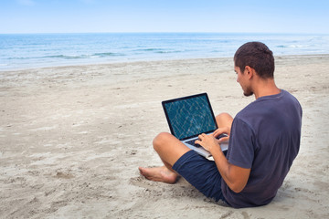 man using computer with wireless internet on the beach