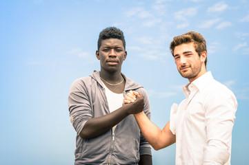 Afroamerican and caucasian men shaking hands against racism