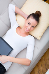 Junge Frau mit Tablet PC auf dem Sofa