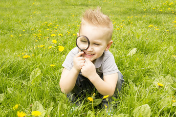 boy looking through a magnifying glass and smile