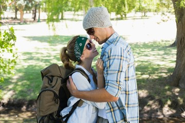 Active cute couple embracing each other on a hike smiling at eac