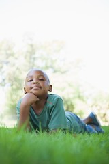 Little boy lying on grass smiling at camera