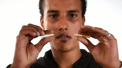 Quit smoking. Young man breaking a cigarette.