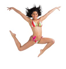Fit girl in bikini leaping and smiling at camera