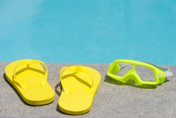 Yellow flip flops and water glasses by the pool
