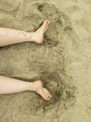 Persona en la playa. Detalle de piernas en la arena.
