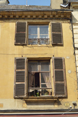 Facade of a decayed apartment with open window shutters