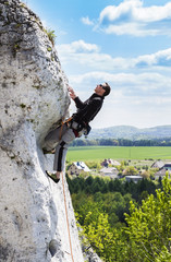 Man climbing natural rocky wall with beautiful view.