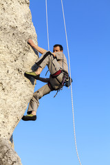 Difficult rock climbing position on horizontal cliff, mountains