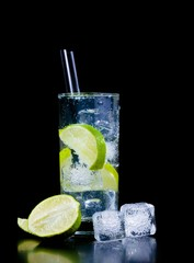 Cocktail with ice and lime slice with straw and space for text