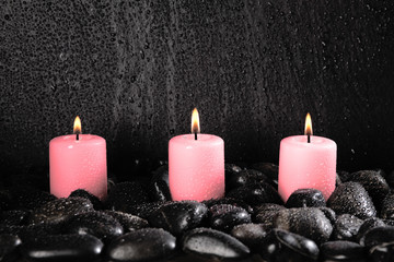 pink candles and pebbles on a black background