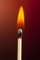 streichholz mit flamme auf rotem hintergrund