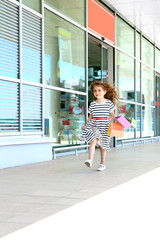 Happy little girl with shop bags, outdoors