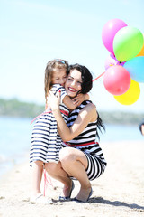 Happy mom and daughter on the beach