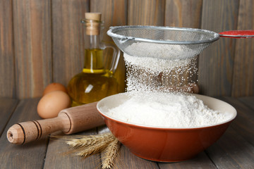Sifting flour into bowl on table on wooden background