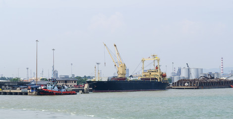 Large vessels carrying goods into the port.