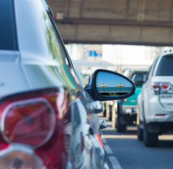 Sea view in side mirror of car with traffic jam