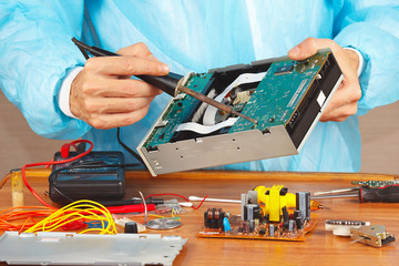 Repair electronic board with a soldering iron in workshop