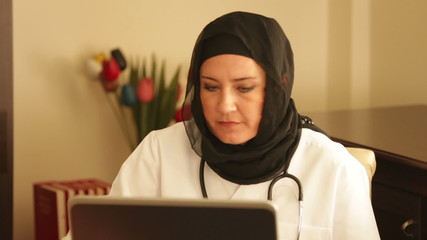Female doctor working with computer in office