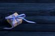 Ein Geschenk mit blauer Schleife auf Holz Hintergrund