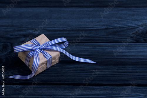 canvas print picture Ein Geschenk mit blauer Schleife auf Holz Hintergrund